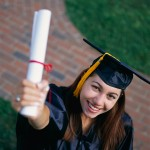 Smiling Graduate Holding up Diploma